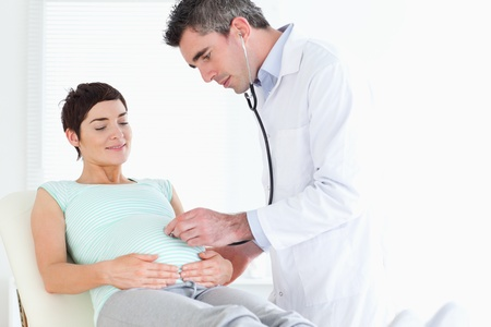 regnant: Doctor listening into the womans tummy with a stethoscope in a room