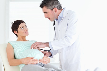 Doctor examining the womans tummy with a stethoscope in a room photo