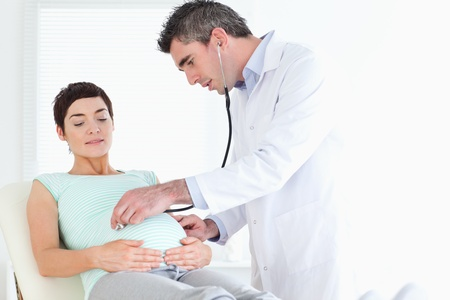 regnant: Doctor examining the cute womans tummy with a stethoscope in a room