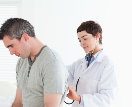 Doctor examining a male patient in a room photo