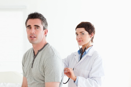 Charming Doctor examining a patient with a stethoscope in a room photo