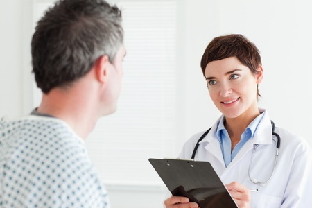 Doctor talking to a male patient holding a chart in a room photo