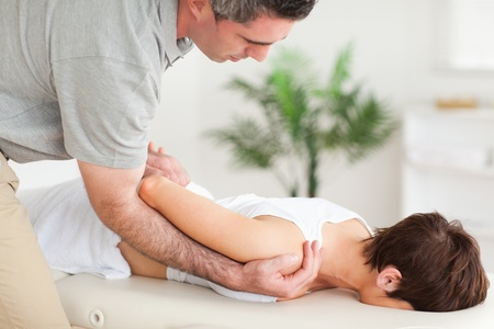 strength therapy: Brunette woman getting a shoulder-stretching in a room Stock Photo