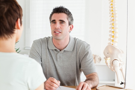 Doctor and patient sitting at a table talking in a room photo