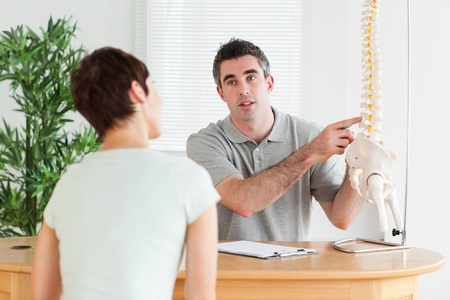 Male Doctor showing a patient a part of a spine in a room Stock Photo - 11190082