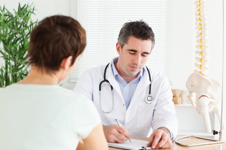 Male Doctor writing something down in a room photo