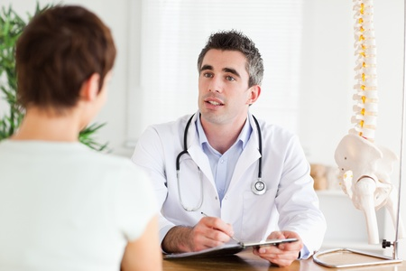 Male Doctor writing something down while patient is talking in a room photo
