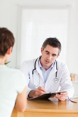 Handsome Doctor talking to a brunette patient in a room photo