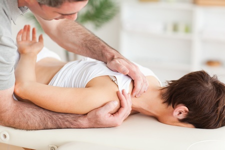 Gorgeous brunette woman getting a shoulder-massage in a room photo