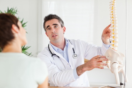 spinal adjustment: Male Doctor explaining something to a woman in a room