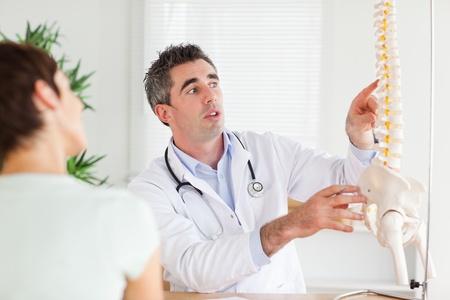 Doctor met een vrouw een deel van een wervelkolom in een kamer