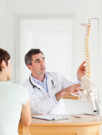 Doctor showing a female patient a part of a spine in a room photo