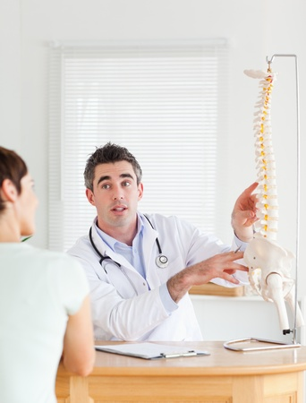 Male Doctor showing a female patient a part of a spine in a room photo