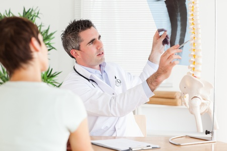 Male Doctor showing a patient a x-ray in a room Stock Photo - 11213791