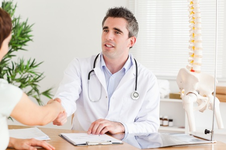 Doctor greeting a patient in a room photo