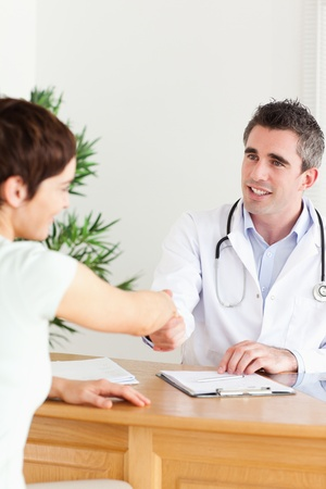 Male Doctor greeting a patient in a room photo