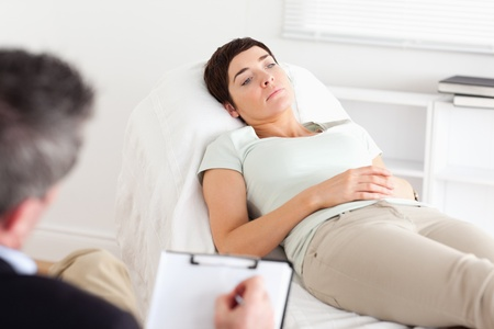 psychotherapy: Male Doctor talking to a female patient in a room Stock Photo