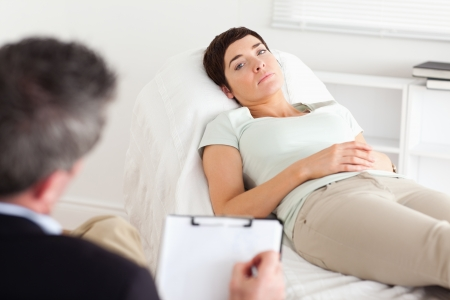 Psychologist talking to a depressed female patient in a room photo