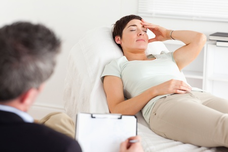 Psychologist talking to a depressed patient in a room