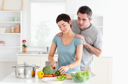 Man massaging his wife while she is cutting vegetables in a kitchen photo