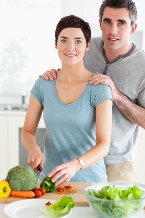 Husband massaging his wife while she's cutting vegetables in a kitchen photo