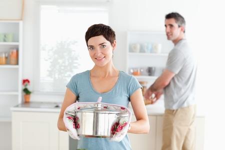 남자가 부엌에서 설거지를하는 동안 냄비를 들고하는 여자