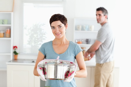 Woman holding a pot while man is washing the dishes in a kitchen photo