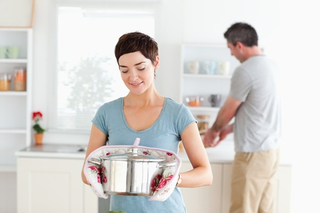 Cute Woman holding a pot while man is washing the dishes in a kitchen photo