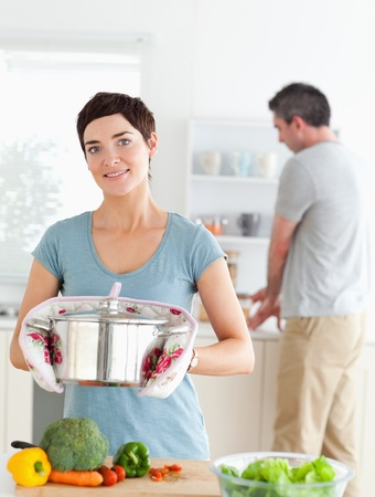 Charming wife holding a pot while her husband is washing the dishes in a kitchen