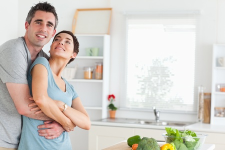 Smiling husband and wife hugging in a kitchen photo