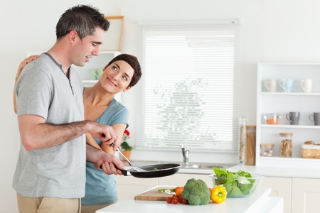 Woman smiling at her husband in a kitchen photo