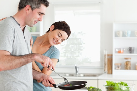Woman looking into a pan her husband is holding in a kitchen photo