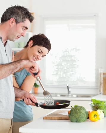 Cute Woman looking into a pan her husband is holding in a kitchen photo