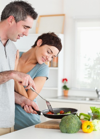 Charming Woman looking into a pan her husband is holding in a kitchen photo
