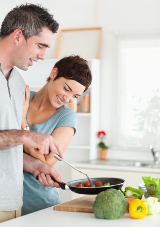 Gorgeous Woman looking into a pan her husband is holding in a kitchen photo