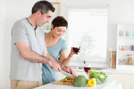 Man cutting vegetables while is woman is watching in a kitchen photo
