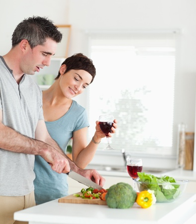 Handsome Man cutting vegetables while is woman is watching in a kitchen photo