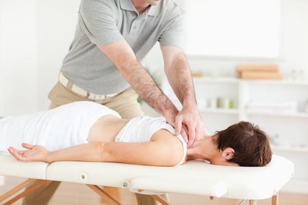 masaje deportivo: Chico masaje del cuello a una mujer linda en una habitaci�n