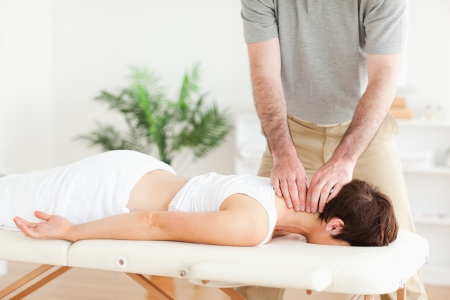 acupressure hands: Guy massaging a brunette womans neck in a room