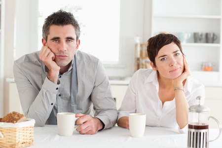 Tired couple drinking coffee in a kitchen photo
