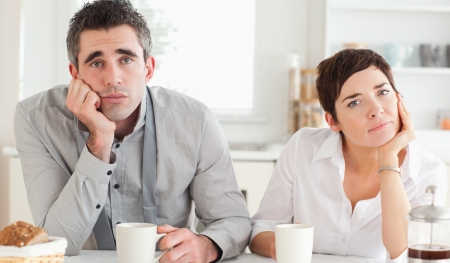 exhausting: Worn out couple drinking coffee in a kitchen Stock Photo