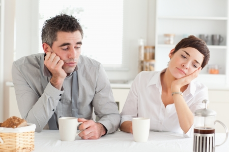 Exhausted couple drinking coffee in a kitchen photo