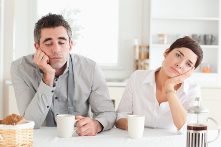 Bored couple drinking coffee in a kitchen photo