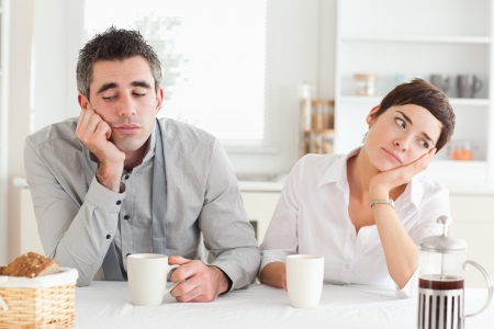 exhausting: Unhappy couple drinking coffee in a kitchen