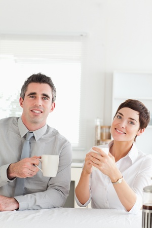 Smiling couple drinking coffee looking into the camera in a kitchen photo