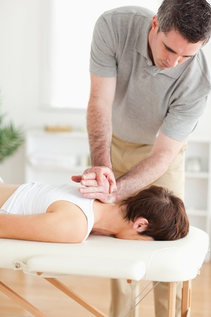 strength therapy: A masseur is massaging a female customers neck in his surgery Stock Photo