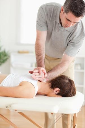 sportmassage: Een masseur is masseren een vrouwelijke klant de nek in zijn praktijk