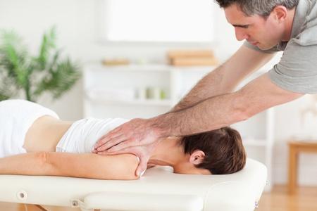 masseur: A masseur is massaging a customers neck in surgery