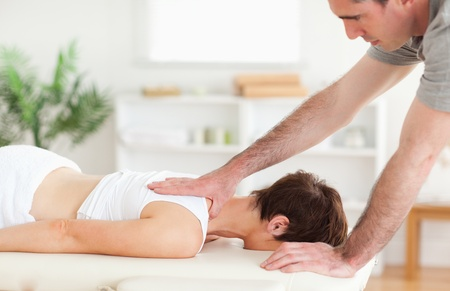 A masseur is massaging a womans back  photo