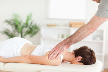 A masseur is massaging a woman's back in his surgery photo